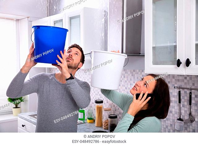 Worried Young Woman Calling Plumber On Cellphone While Man Collecting Leakage Water From Ceiling