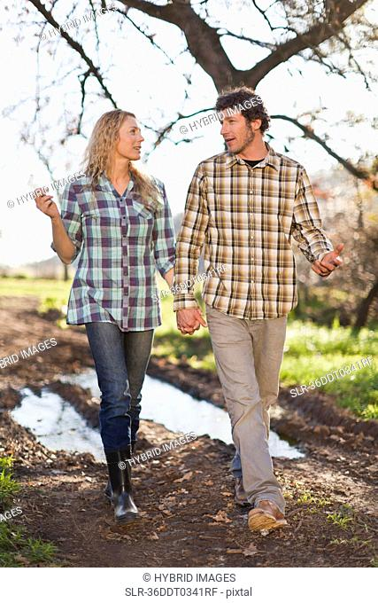 Couple walking hand-in-hand on dirt path