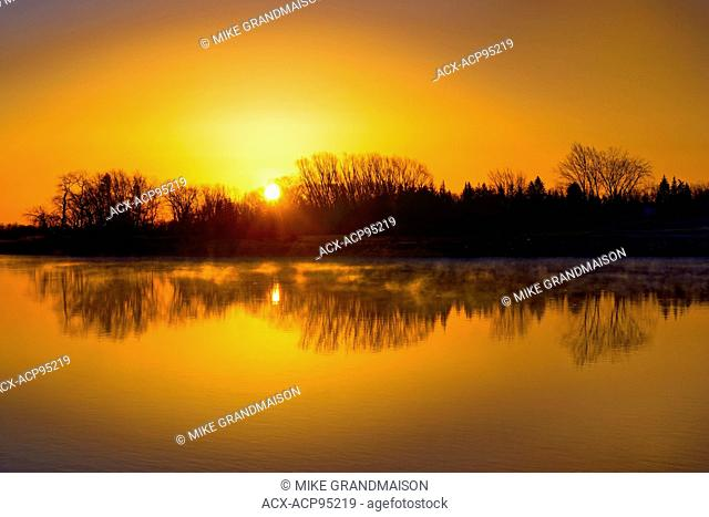 Reflection of trees in Red River at sunrise Lockport Manitoba Canada