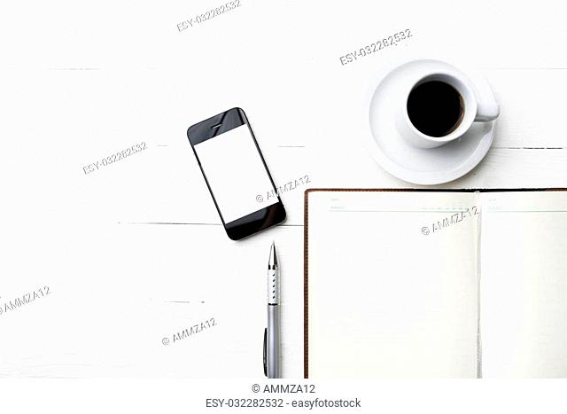 cellphone with notebook and coffee cup over white table