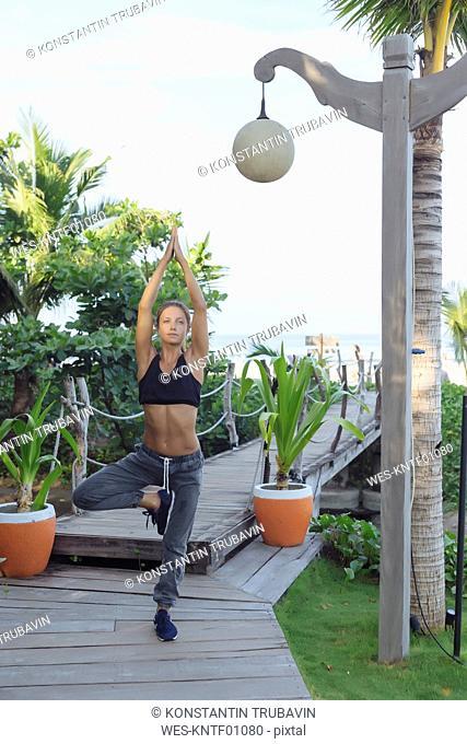 Indonesia, Bali, woman practicing yoga, tree position