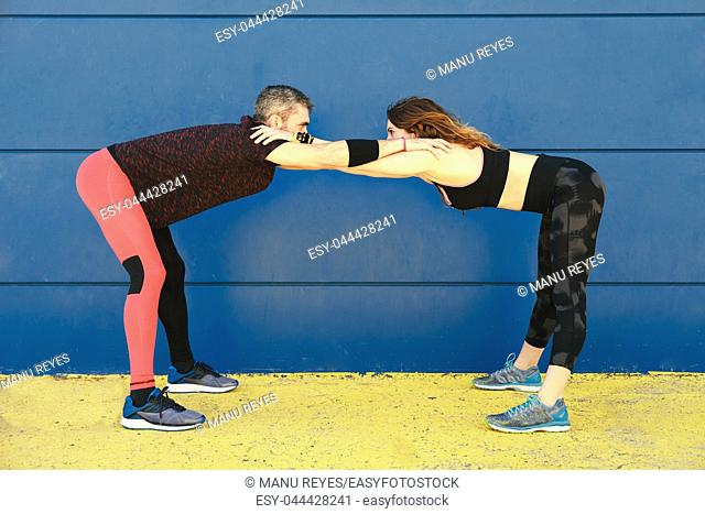 young couple stretching together in front of a blue wall before running