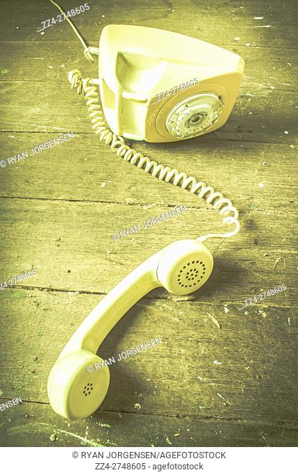 Vintage 1960s rotary telephone off the hook over worn out and dented wooden floor. Break in communication