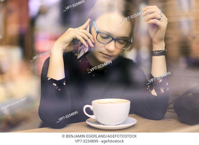 woman behind glass window sitting in coffee shop and calling with phone, listening to phone conversation, closed eyes, in Munich, Germany