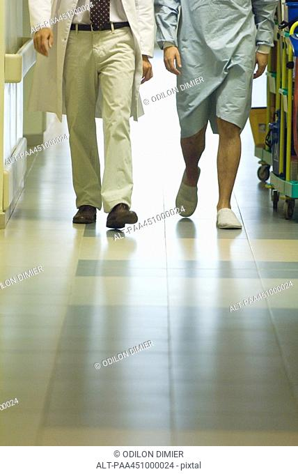Male doctor walking with patient in hospital corridor, cropped view of legs