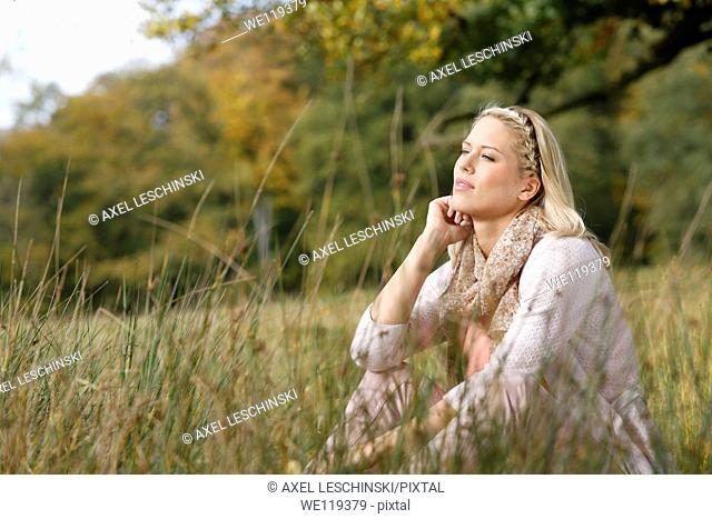 Woman sitting at meadow