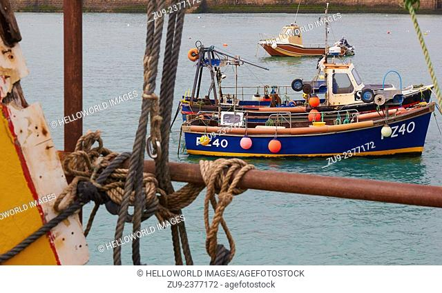 Fishing boats seen through old mooring ropes from Smeaton's Pier, St Ives, Cornwall, England, Europe
