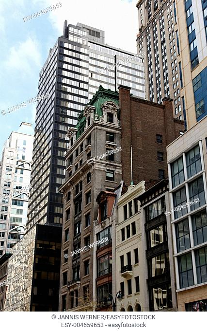 The vastly architecture styles of different ages blending into the chaos that is midtown Manhattan on 5th Avenue