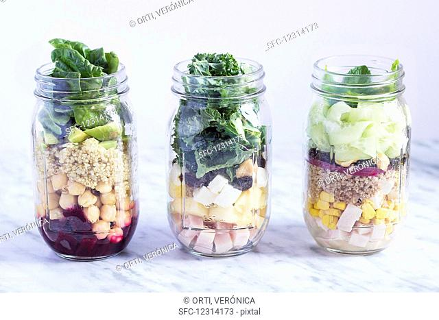 Different layered salads in glass jars