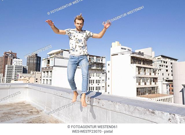 Barefooted man jumping from balustrade of a rooftop terrace