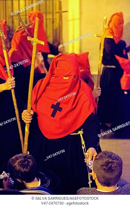 A brother gives candy to a child who is watching the Holy Week Procession, Alzira, Valencia, Spain