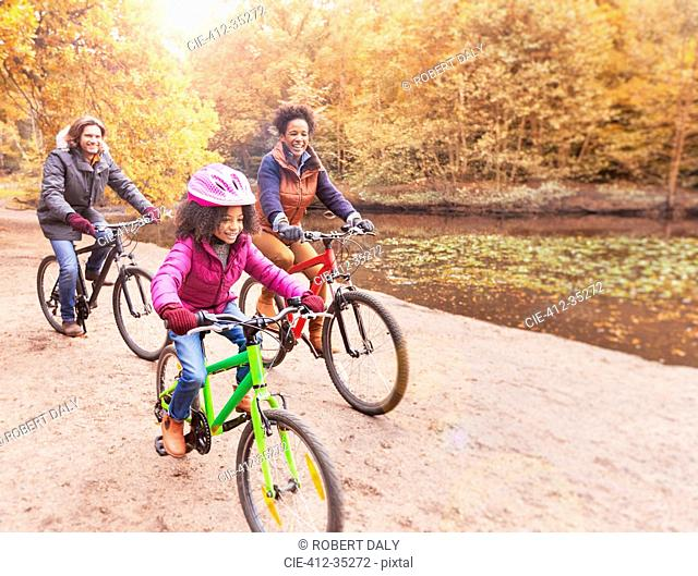 Young family bike riding along pond in woods