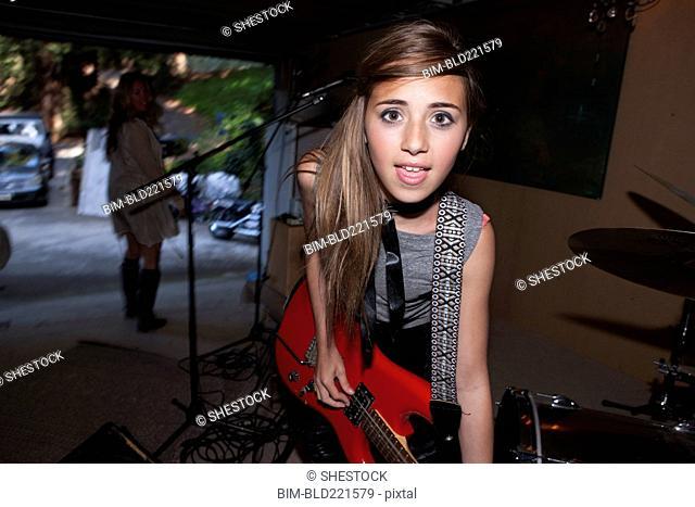 Girl playing guitar in rock band