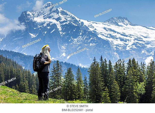 Caucasian woman wearing crown of flowers admiring scenic view of mountain
