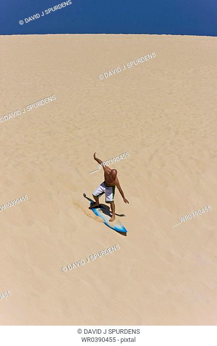Surfer riding large surf dune on surf board