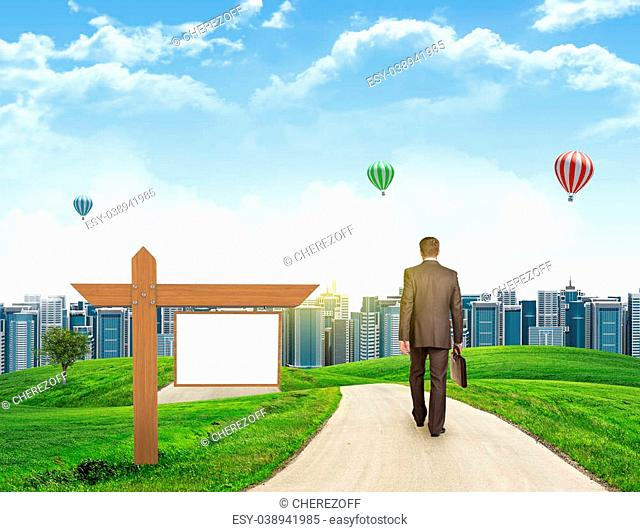 Businessman walks on road. Rear view. City skyline, grass field, wooden signboard and sky in background. Business concept