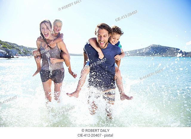 Family running in water on beach