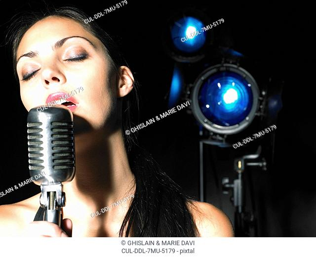 Close up of woman singing into microphone
