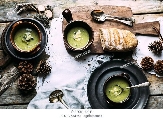 Zucchini soup in 3 bowls on a wooden table with autumn decorations from the wood