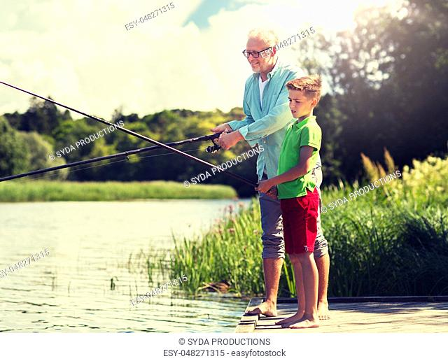 grandfather and grandson fishing on river berth