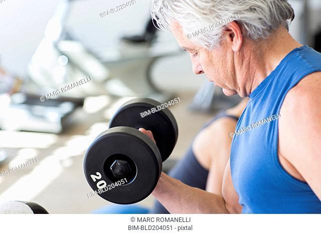 Older Hispanic man lifting weights in gym
