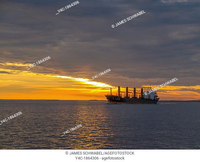 Ocean going freighter ship heading out to sea with sunset sky