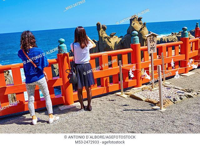 Two japanese girls taking a photo to the Sea of Hyuga at the terrace of Udo-Jingu Shrine. Nichinan City. Miyazaki Prefecture. Japan