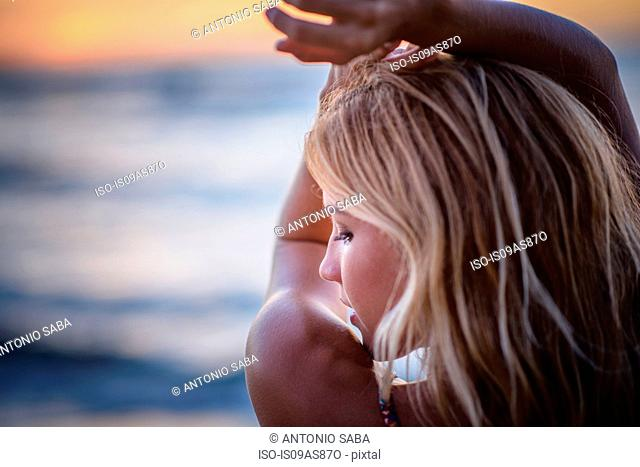 Young woman with arms raised on beach at sunset