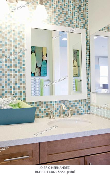 View of taps with mosaic wall and mirror in the bathroom at home