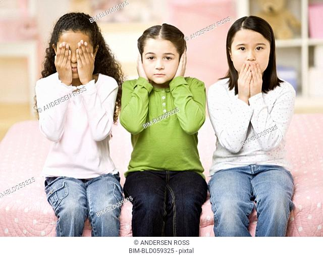 Multi-ethnic girls covering eyes, ears and mouth