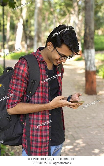 Smiling young boy with backpack looking at his smart phone and texting
