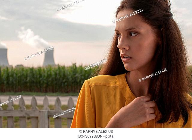 Pensive woman looking away with nuclear power station in background