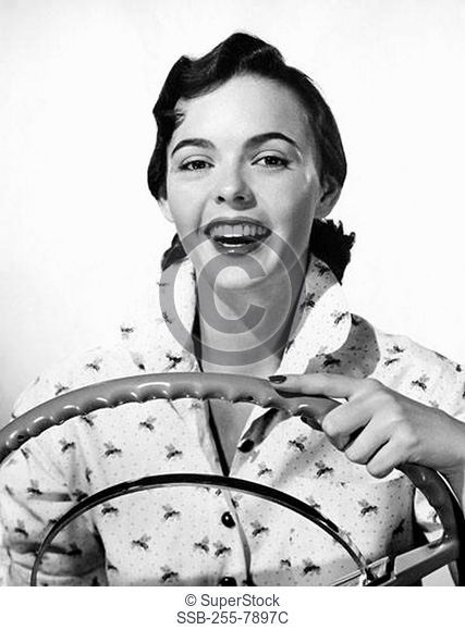 Portrait of young woman holding car steering wheel