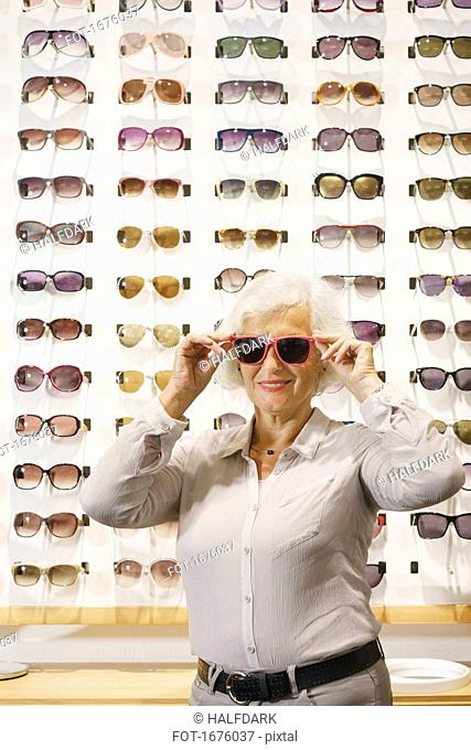 Portrait of senior woman wearing sunglasses while standing at store