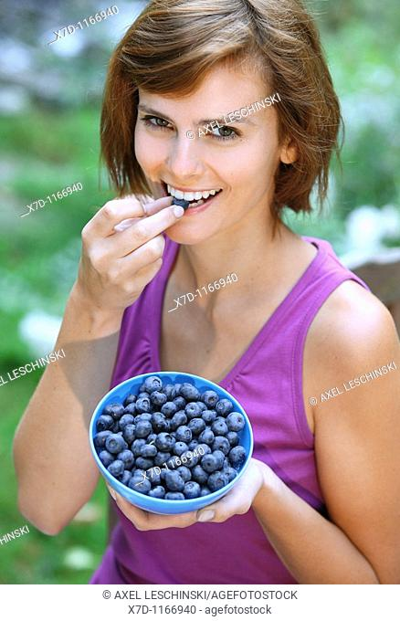woman sitting in the garden eating blueberries and currants