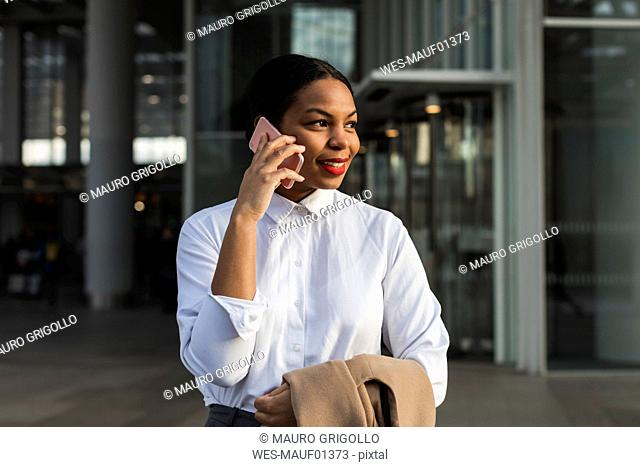 UK, London, portrait of smiling businesswoman on the phone