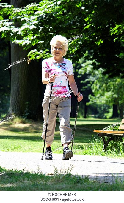 a elderly woman is walking in a park with walking staves