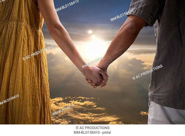 Caucasian couple holding hands in dramatic sunset sky