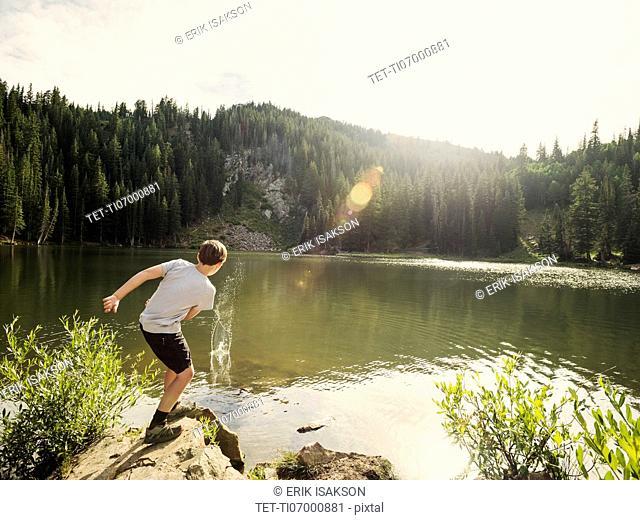 Boy (12-13) throwing stone into lake