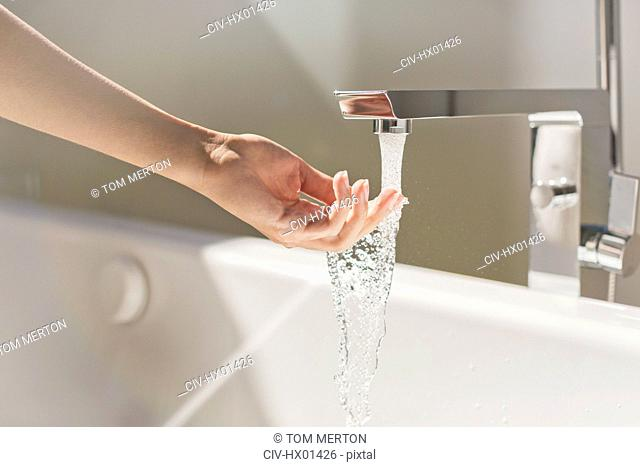 Woman touching water from modern bathtub faucet