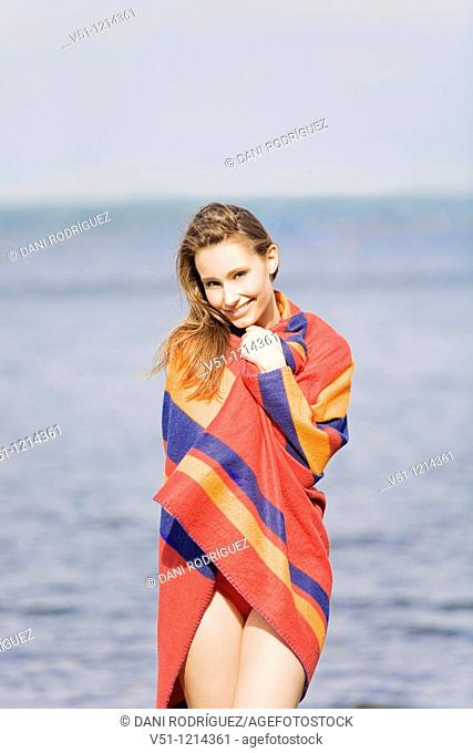 Portrait of a young woman standing by the sea and covering with a blanket