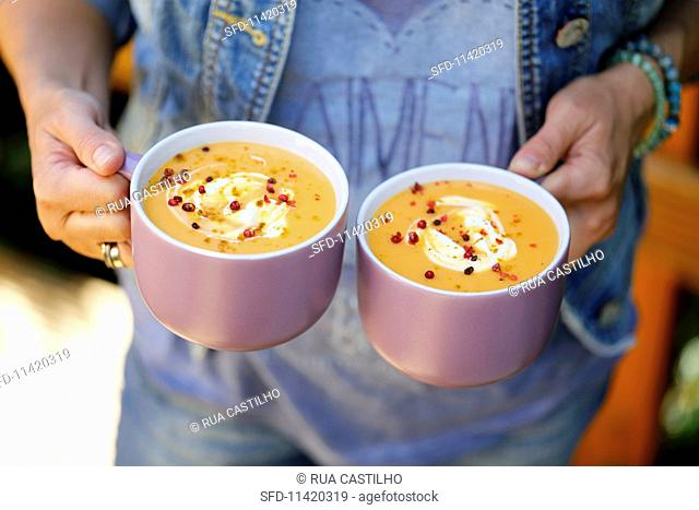 A woman holding two cups of cream of pumpkin soup with curry