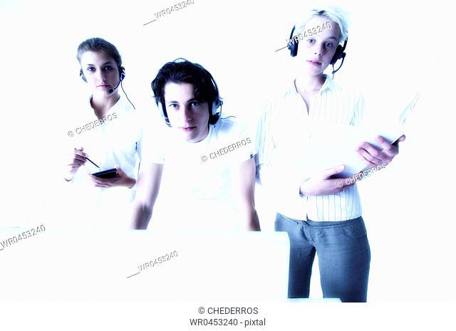 Businessman standing between two businesswomen using a computer