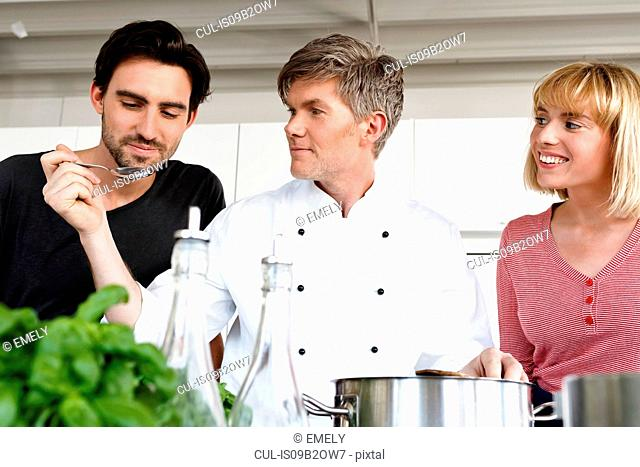 Chef and couple in kitchen tasting food