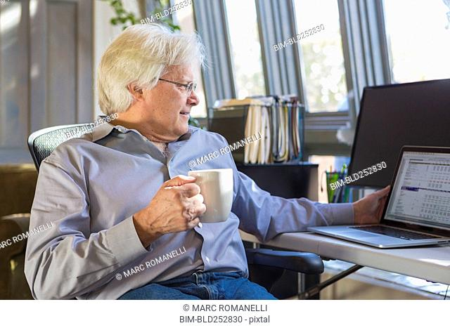 Caucasian man drinking coffee and using laptop