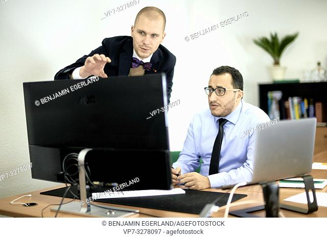 business man teaching employee, manager explaining new concept at computer screen in office at work, in Cottbus, Brandenburg, Germany