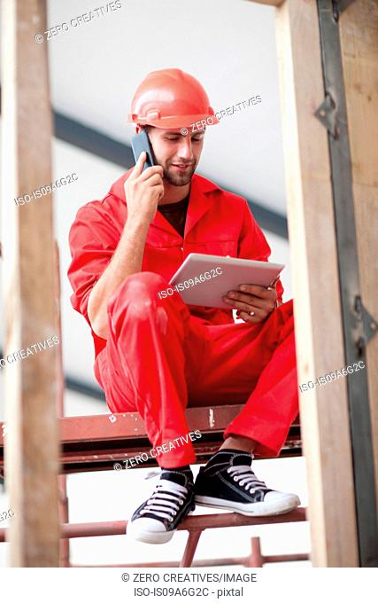 Builder with digital tablet talking on phone on construction site