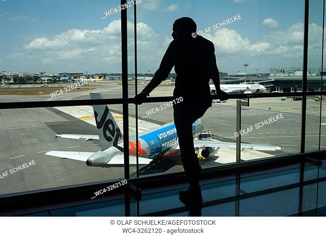 Singapore, Republic of Singapore, Asia - A visitor is looking at a Jetstar Airbus A320 from the Terminal 1 viewing mall at Singapore's Changi Airport