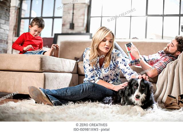 Couple and son relaxing with dog at home