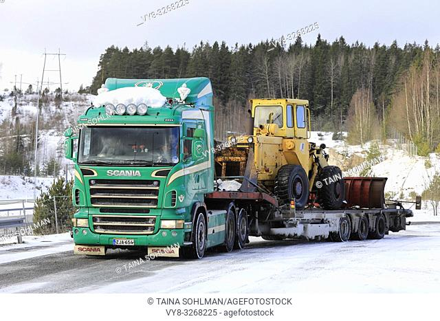 Salo, Finland - March 9, 2019: Green Scania truck with Noteboom low loader trailer carrying old wheel loader ready for transport on a day of winter